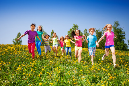 playing field: Running happy kids holding hands in green meadow during summer
