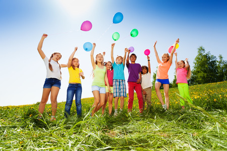 people and nature: Jumping kids with flying balloons in the air in green field in summer