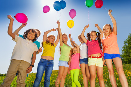 Children standing in half round with arms up to flying balloons in green field Imagens