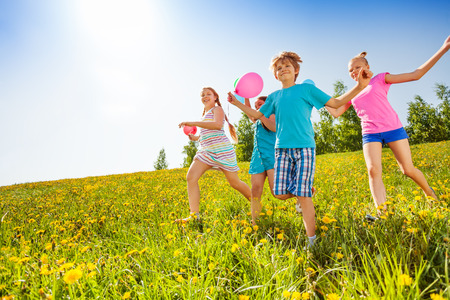 Excited children with balloons run in green field in summer
