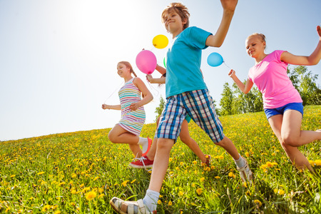 Happy children with balloons run in green field with yellow flowers in summer photo