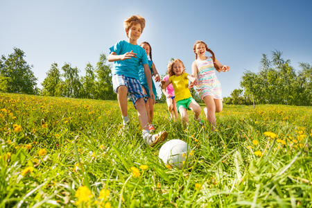 Happy kids playing football in green field in summer Stock Photo