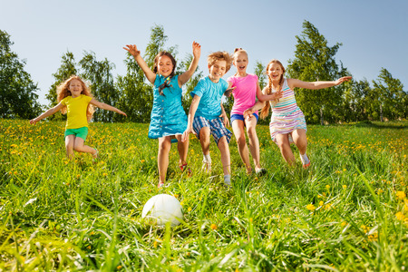 Playful friends running to the ball in yellow meadow in summer photo