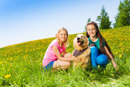 Two girls sitting near to dog on green grass with yellow flowers in summer photo