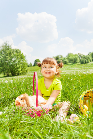 Positive girl with rabbit sitting on the grass in park during summer time photo