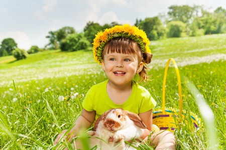 Smiling girl with flowers circlet with rabbit in the basket sitting in the park in summer