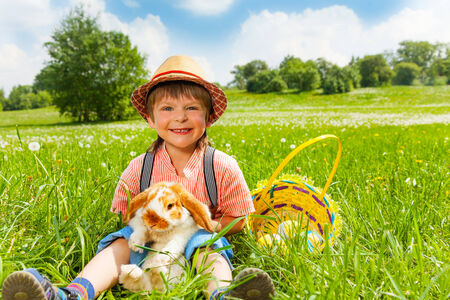 Small boy wearing hat and hugging rabbit while sitting on green field in summer time photo