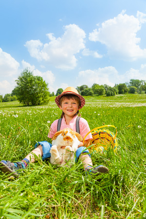 kids wear: Positive boy wearing hat and hugging rabbit in green park Stock Photo