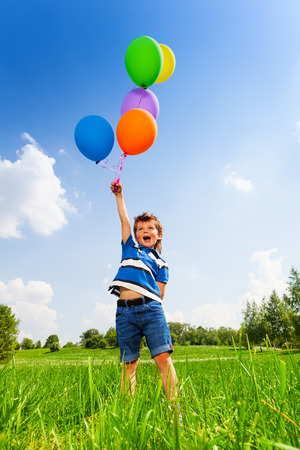 weather balloon: Excited boy with colorful balloons in green meadow in summer