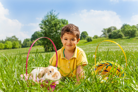 Boy with rabbit and two baskets in the park in summer photo