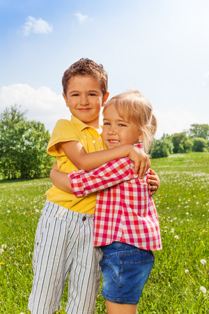 Boy and girl hugging each other in green field in summer photo