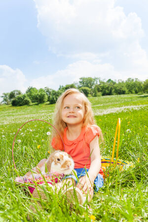 Happy girl with rabbit in the basket sitting in the park in summer photo