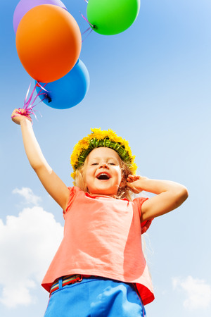 circlet: Positive girl with balloons wears flower circlet in summer Stock Photo