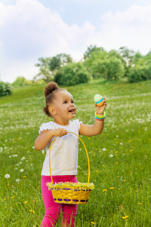 Positive small girl with eastern egg and basket in green field in summer