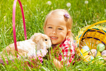 Cute small girl cuddling rabbit in green field with basket with Eastern eggs nearby