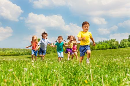 夏の時間の間に緑の野原で幸せな子供たちを実行