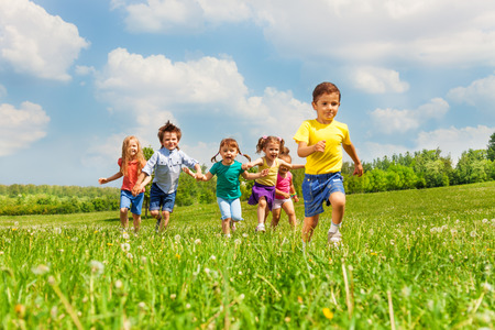 children playing: Running happy kids in green field during summer time