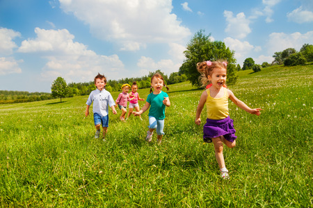 Running happy children in green field during summer time