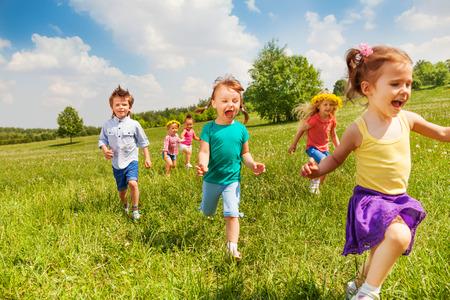 Emocionado correr los niños en el campo verde en el juego de verano juntos