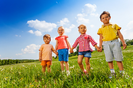children holding hands: Four children holding hands and standing together in green field in summer