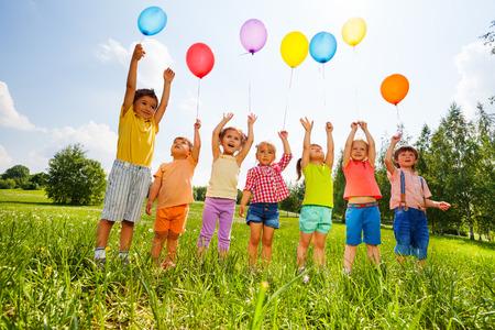 Šťastné děti s balónky a ruce nahoru na obloze v zeleném poli