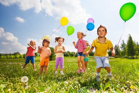 Kinderen met kleurrijke ballonnen die op gebied in de zomer Stockfoto
