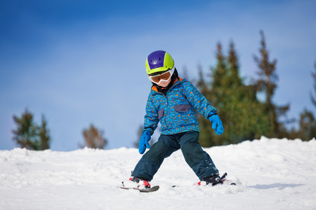downhill skiing: Small boy in ski mask and helmet learns skiing