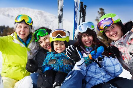 Positive friends with kid together wear ski masks photo