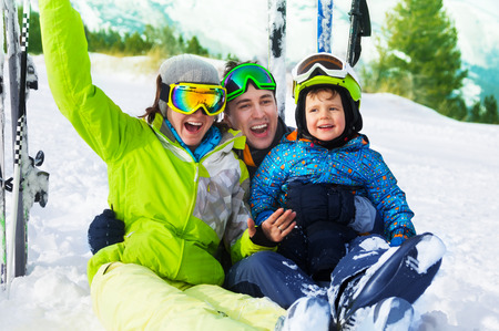 Happy parents and boy with ski masks sit on snow photo