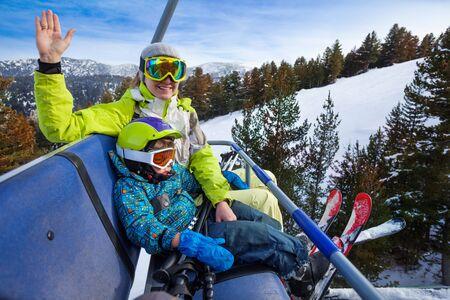 kids at the ski lift: Happy mom and boy in ski masks seat on elevator