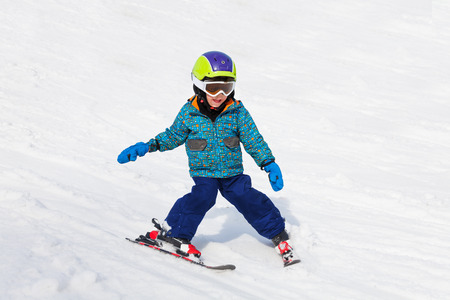 スキー用マスクの笑みを浮かべて少年が学ぶスキー 写真素材