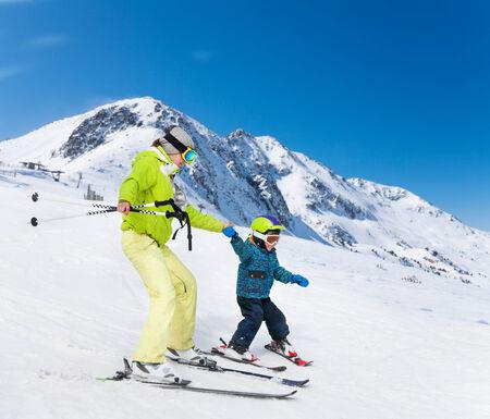 インストラクターと山を下ってスキーの子供