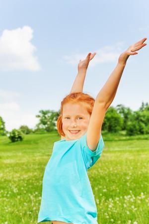 Beautiful little girl raises hands photo
