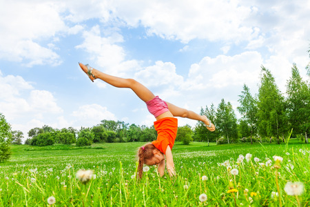 Little girl doing gymnastics on grass photo