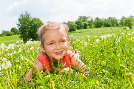 Pretty little girl laying on the grass photo