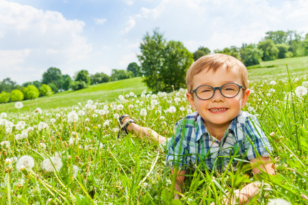 Little boy smiles laying on a grass photo