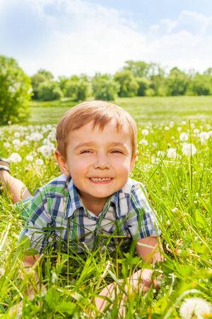 sandal tree: Nice boy smiles laying on a grass