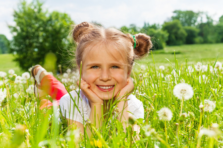 Nice girl smiles laying on a grass photo