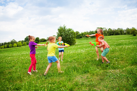 Children play with water guns on a meadow photo