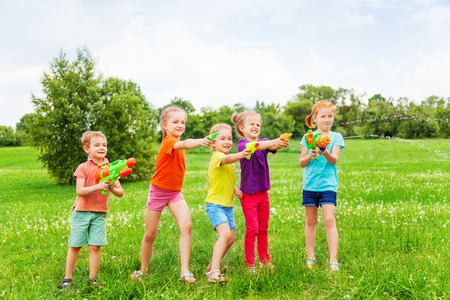 kids playing water: Kids playing with water guns on a meadow