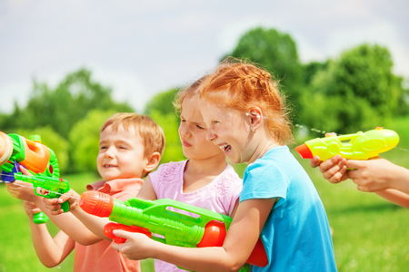 Funny kids playing with water guns photo