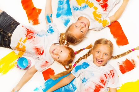 Three little girls laying on the painted floor photo