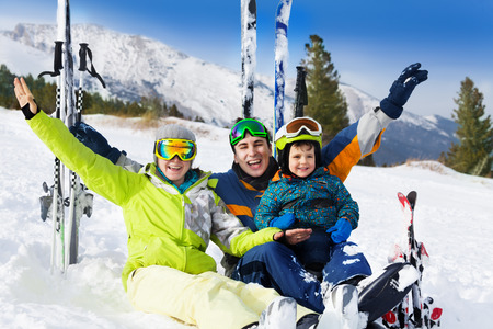 Happy family with hands up on snow after skiing
