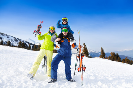 Mom, dad with child on his shoulders in ski masks photo