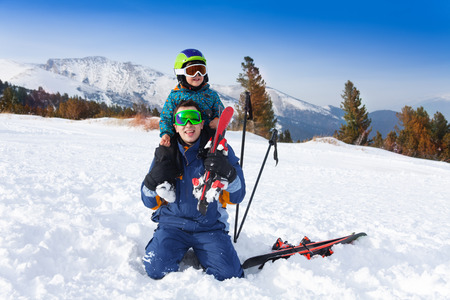 ski mask: Smiling father in ski mask with son on shoulders Stock Photo