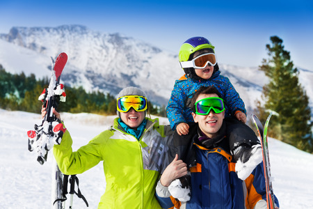Parents and child on dad s shoulders in ski masks photo
