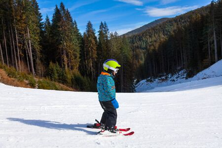 Small boy in ski mask standing and skiing photo