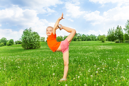 Beautiful little girl doing gymnastics on a grass
