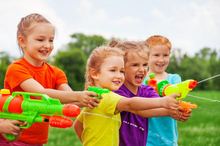 kids playing water: Kids play with water guns on a meadow