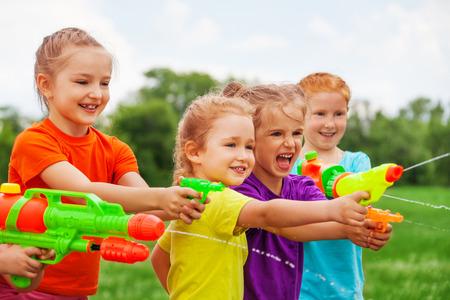 pistolas: Los niños juegan con pistolas de agua en un prado